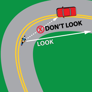 Rider in curve, oncoming car, arrows pointing where to look and where not to look